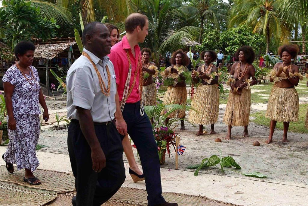 Women in traditional attire perform as William and Kate arrive at Marapa Island.