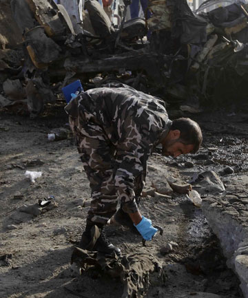 DEADLY ATTACK: An Afghan security officer investigates at the site of a suicide attack in Kabul.