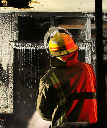 DAMPENING DOWN: Fire crews douse the burnt out house on Barbadoes St in Christchurch.