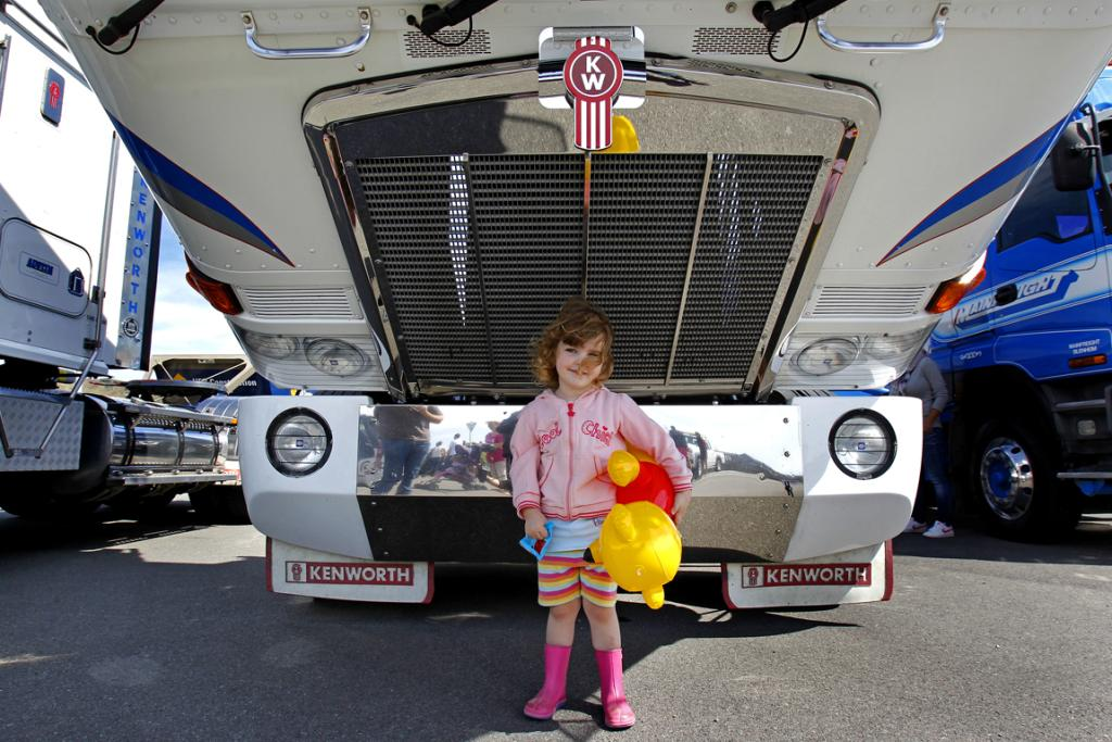 Bella Price, 3, stands under a tilted trucks cab.
