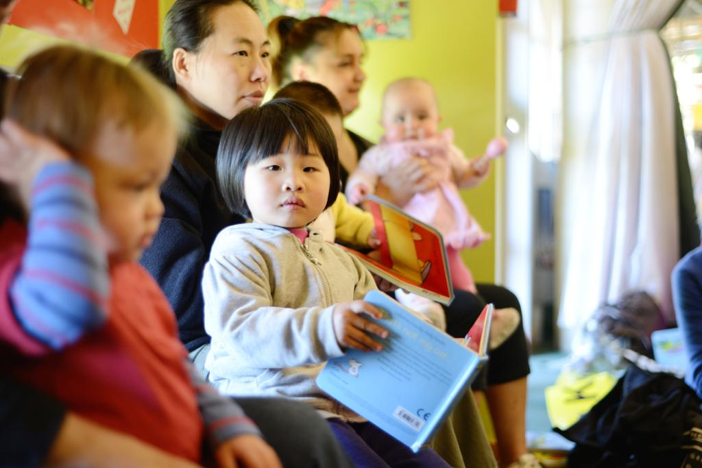 Grace Cao, 3, reads a book during story time at Baby Rock and Rhyme at the Ruth Gotlieb Library.