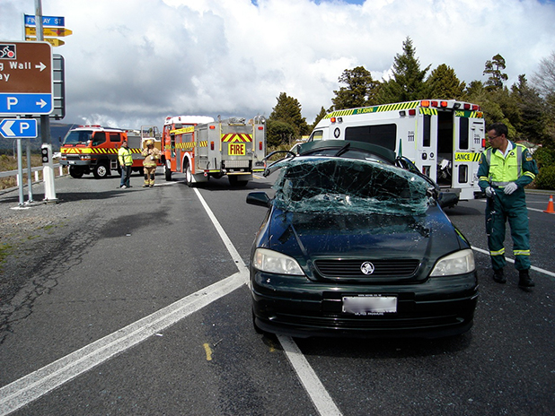 CRASH SITE: Emergency services work at the scene of a two car crash on State Highway 4 near National Park on Monday.