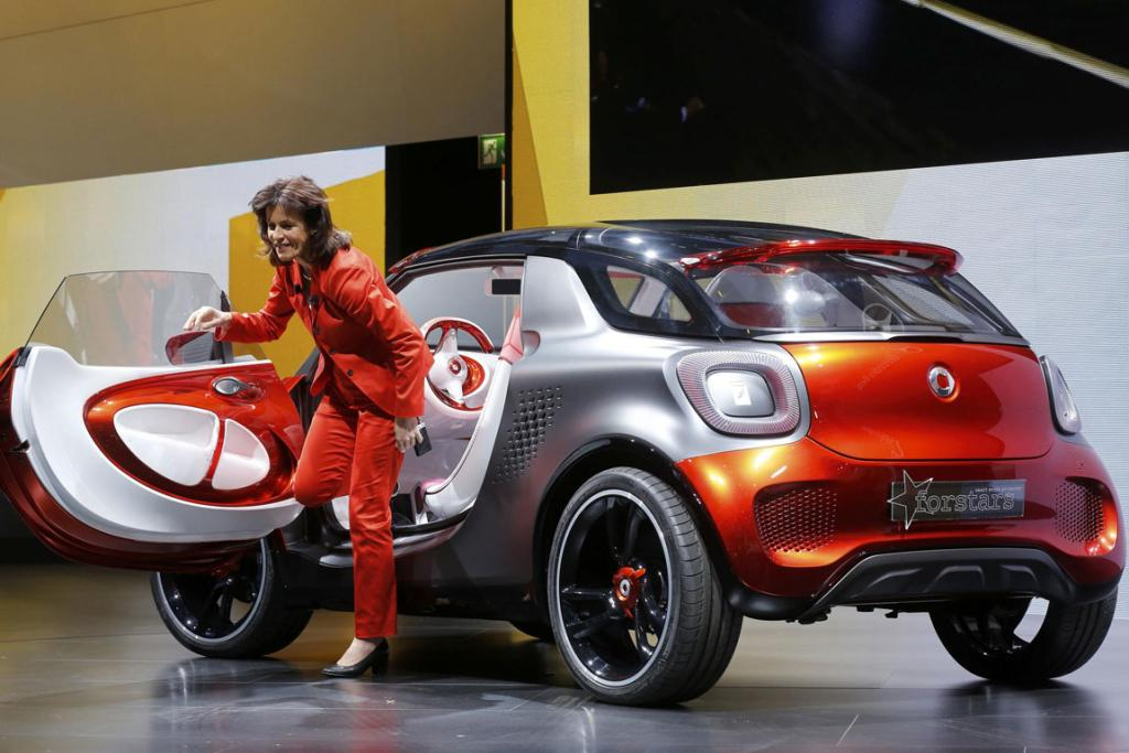 Annette Winkler, head of Smart brand arrives on stage with a Smart ForStars model at the Paris Motor Show.
