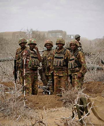 READY TO MOVE: Soldiers of the Kenyan Contingent serving with the African Union Mission in Somalia stand at a mortar position outside the Somali port city of Kismayo.