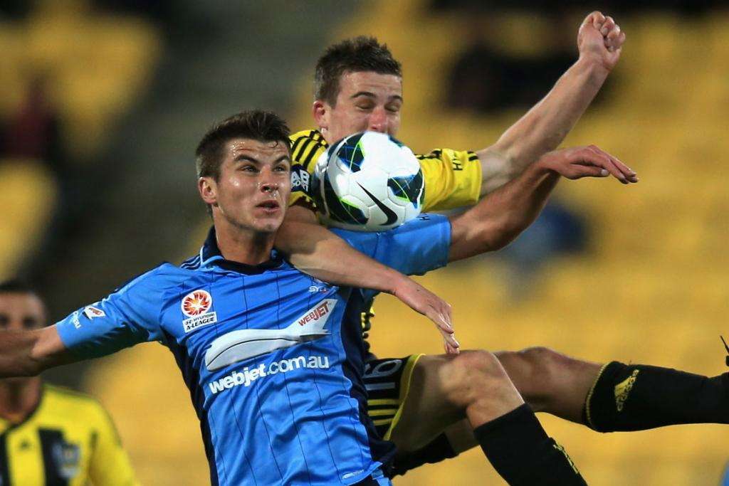 Terry Antonis of Sydney FC and Louis Fenton of the Phoenix compete fort he ball.