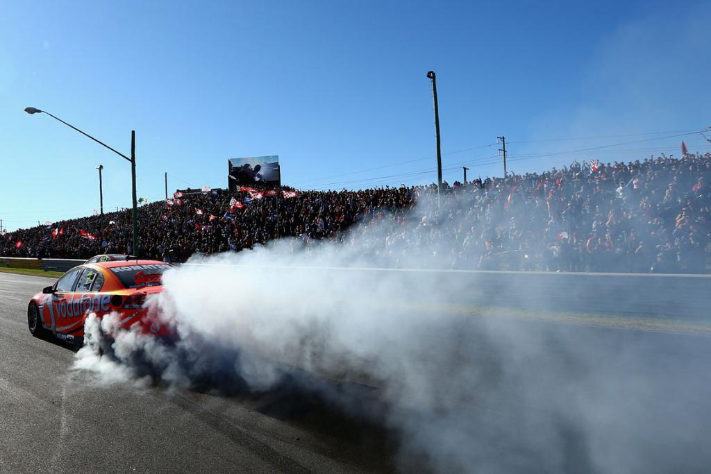 Jamie Whincup driver of the #1 Team Vodafone Holden celebrates with a burnout after winning the Bathurst 1000.