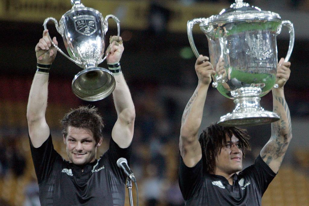 Richie McCaw holds up the Tri-Nations trophy next to teammate Rodney So'oialo with the Beledisloe Cup after they won the Tri-Nations rugby match against Australia in 2008.