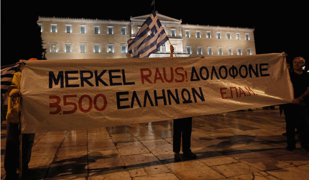 AUSTERITY ANGER: Protesters hold a banner in front of the Greek parliament during a rally against the upcoming visit by German Chancellor Angela Merkel.