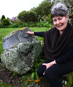 Adrienne O'Sullivan rests her hand on a stone sculpture created as a memorial to husband Terry. His death in 1997 propelled her development of the family's Okato garden.
