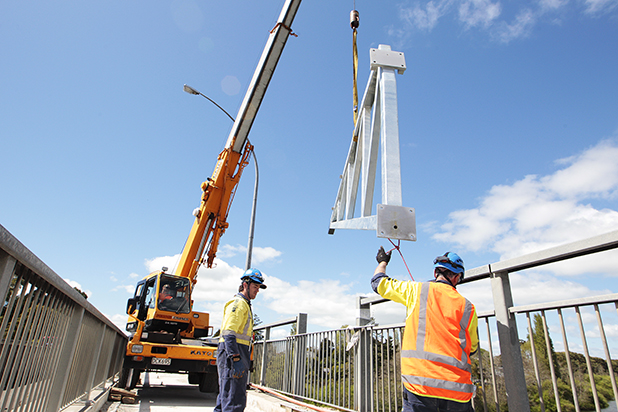 DELICATE WORK:  A crane lowers a clip-on frame off Hamilton's Pukete Bridge. Framing pairs are being attached to the southern side of the bridge to support a new clip-on pedestrian and cycle lane.