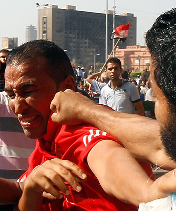FISTS FLY: A member of the Muslim Brotherhood and supporter of Egypt's President Mohamed Mursi punches an anti-Brotherhood protester at Tahrir Square, the focal point of the Egyptian uprising, in Cairo.