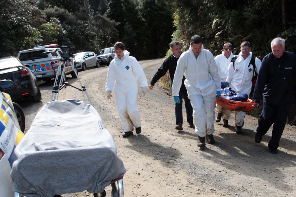 Police remove the bodies of the two men found in an abandoned mine in dense scrub in the Coromandel Peninsula.