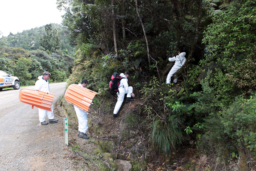 Police head into the dense scrub to recover the bodies of the two men.