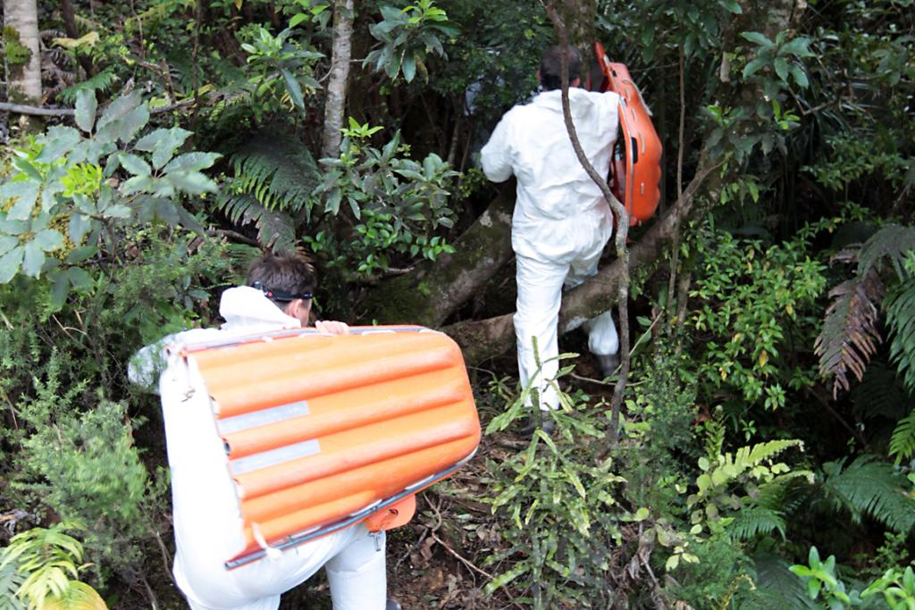 Police head into the dense scrub to remove the bodies of the two men found in an abandoned mine in the Coromandel Peninsula.