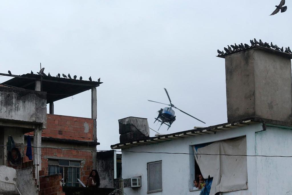 Residents look on as a police helicopter patrols the Manguinhos slum