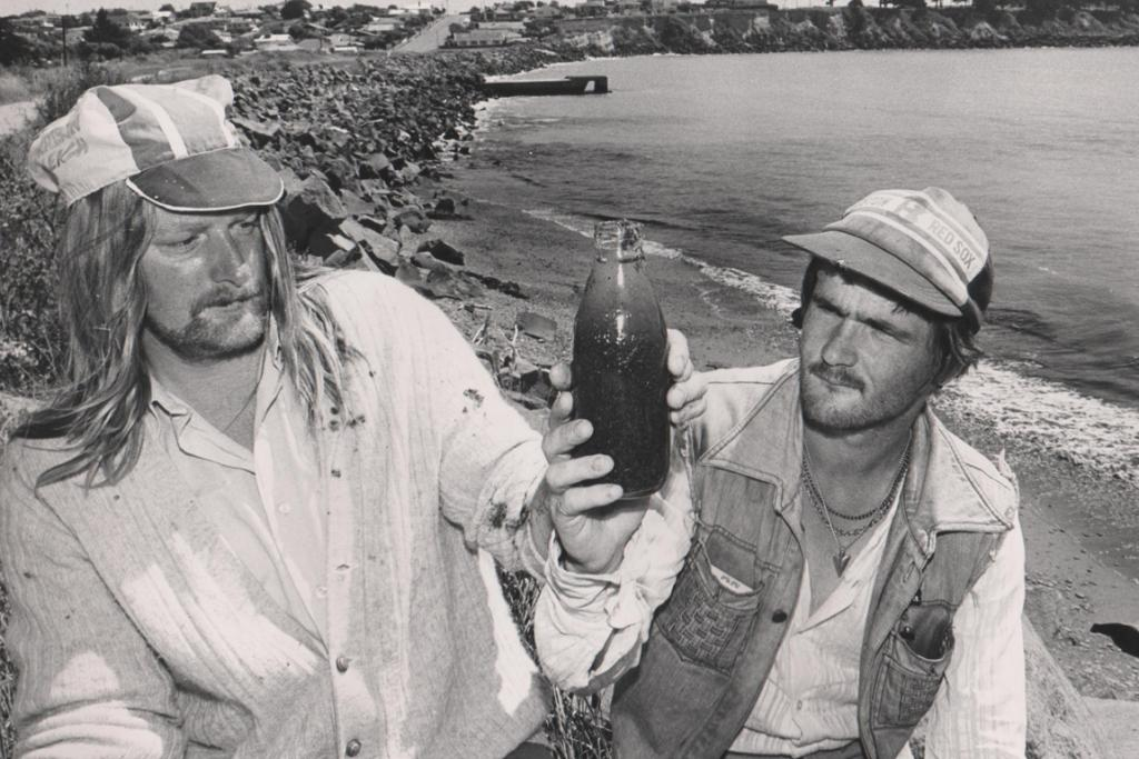 MESSAGE IN A BOTTLE: This bottle seems to be intriguing the two men in this photo. Who are they and why is the bottle so interesting? Do you know?