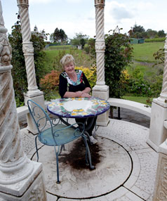 "Pat Ekdahl sits in the white rotunda which is the feature in an area named ""the fairy garden""."