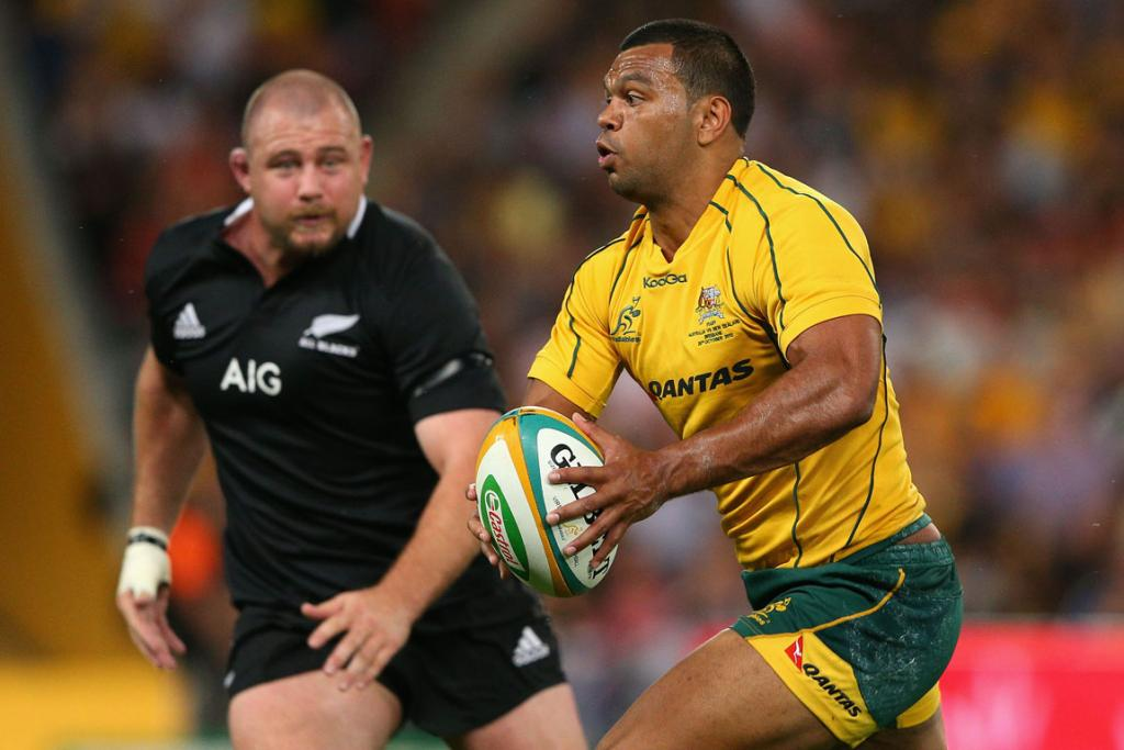 Kurtley Beale runs the ball under close attention from All Blacks' prop Tony Woodcock.