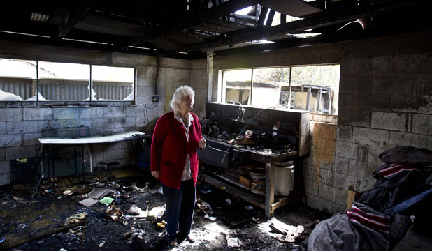 DISTRAUGHT: Bromley retiree Lorna in the remains of her garage, which had been filled with her entire household of belongings until arsonists targeted her property early on Sunday.