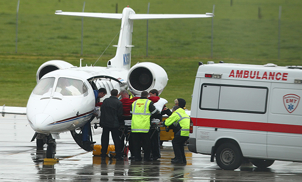 HEADING HOME: Kirsten Steinke, covered in a red blanket, was wheeled from an ambulance and carefully loaded on a Lear jet at Hamilton Airport yesterday.