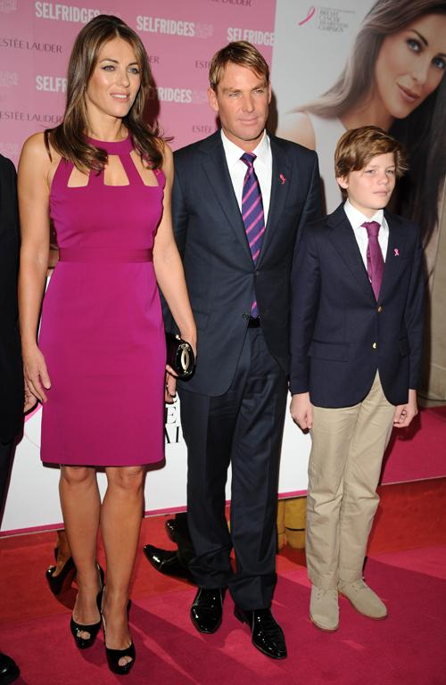 Just a week later she pops up in pink again in London, seen here with her bloke Shane Warne and her son Damian.