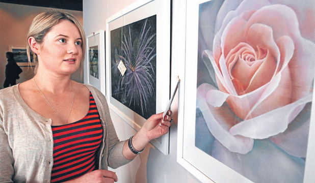 ON SHOW: Southland Museum and Art Gallery graphics technician Jane Watkinson does a final check on a work by guest artist Julie Freeman, showing in the Southern Pastel Artists Group ILT Positively Pastels Art Awards.