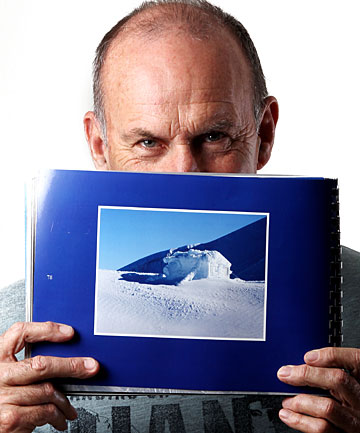 Jim Hickey shows off an image in a new book of weather photographs taken by New Zealanders