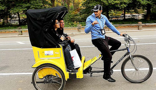 Tourists ride in a New York City pedicab through Central Park