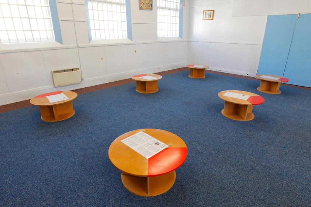 Tables set up in the visitor's room. The prisoners have to sit in front of the orange triangle.