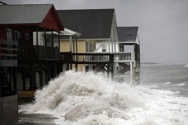 A wave crashes over the protecting sandbags in front of the houses on the east side of Ocean Isle Beach, North Carolina.