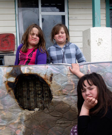 LUCKY ESCAPE: From left, twins Jorja and Toni Hughes, 8, and Mikayla Hughes, 9,  with the mattress that caught alight in a fire caused by an electric blanket in Invercargill on Sunday morning.