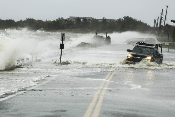 A truck drives through water pushed over a road by Hurricane Sandy in Southampton, New York.