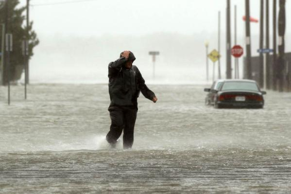 Bracing against the wind, a man wades through a street flooded during Hurricane Sandy in Ocean City, Maryland.