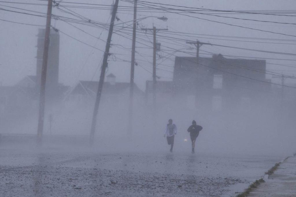 Two boys run down Foster Avenue while dodging high winds and waves from the effects of Hurricane Sandy in Marshfield, Massachusetts.