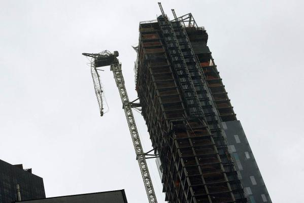 A crane hangs from a building after being damaged in winds from Hurricane Sandy in New York.