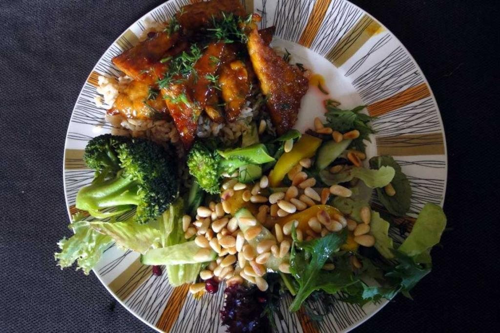 Orange Pan-glazed Tempeh with brown rice, steamed broccoli and green salad with pomegranate seeds and toasted pine nuts.