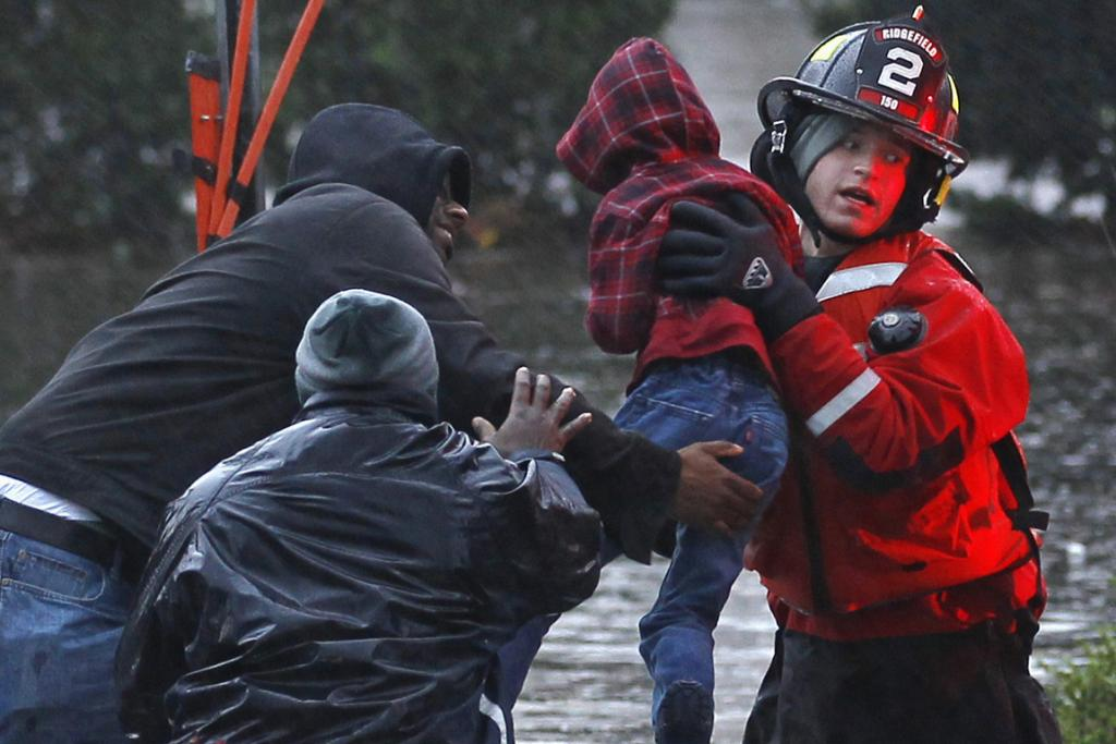 Residents, including a young child, are rescued by emergency personnel from flood waters brought on by Hurricane Sandy in Little Ferry, New Jersey.