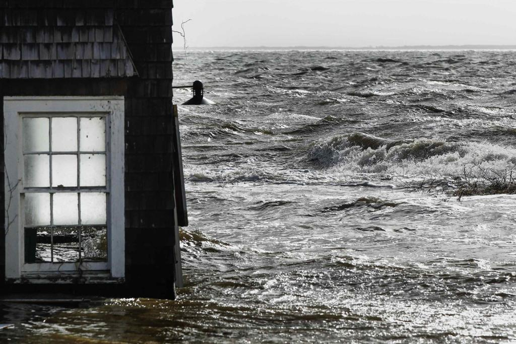 Water pushed up by Hurricane Sandy splashes into the window of a building standing by the shore in Bellport, New York.