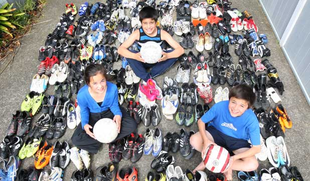 BOOT DRIVE: Charlotte Lowe, left, Jaylen Rodwell and Callum Lowe  have been helping to collect more than 120 pairs of boots to help under-privileged children get involved with sports.