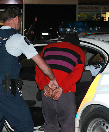 IN CUSTODY: A man is taken away by police after an alleged assault in the Marlborough Sounds.