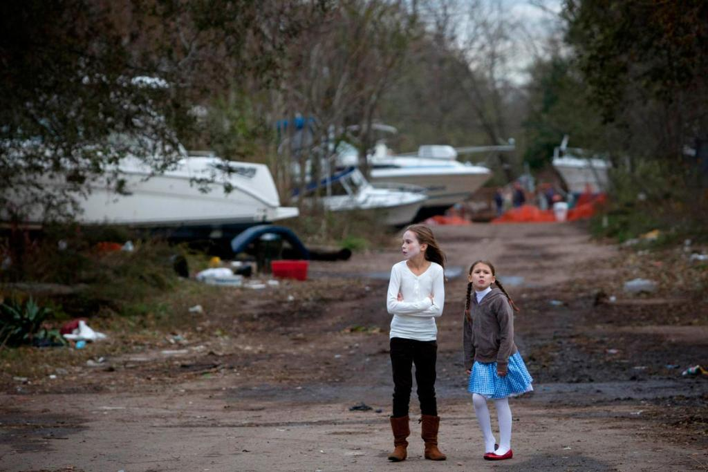 Two girls examine the wreckage of boats washed ashore in Great Kills, Staten Island, New York.