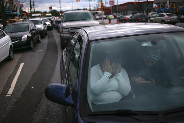 A woman covers her face in frustration while waiting for hours in line to get fuel outside at a petrol station in the New York City borough of Queens.
