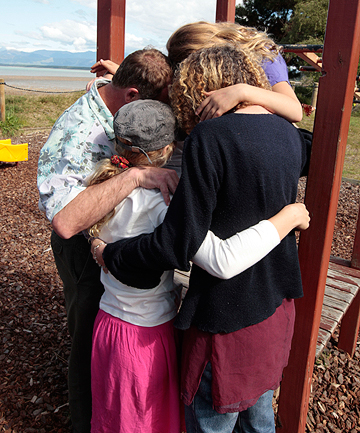 TOGETHER AT LAST: A family hug at the McKee Domain, Ruby Bay, after almost a year spent battling charges that the father indecently assaulted one of his daughters at the domain.