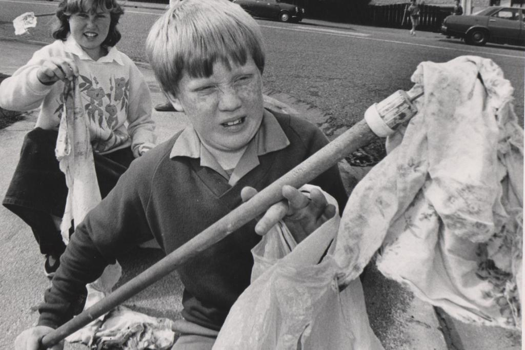 YUCK: What's causing the look of disgust on this boy's face? This photo remains a mystery –  and seems a gross one. What have these children discovered?