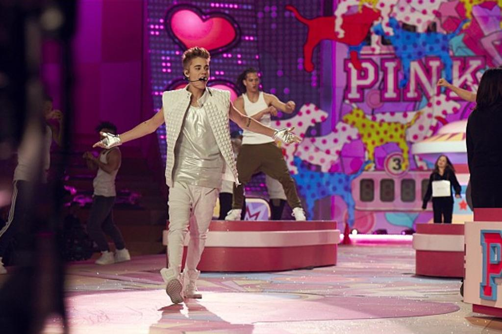 Justin Bieber performing for the crowds and models.