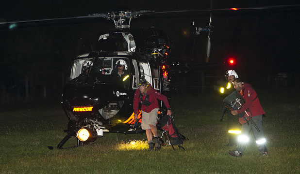 Emergency services workers land at Cardrona Valley after the wreckage of the crashed helicopter was found.
