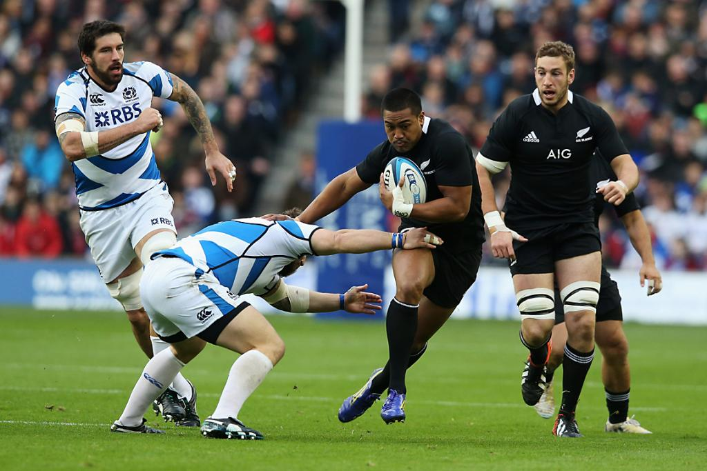 Julian Savea, of the All Blacks, is tackled by Scotland's Ryan Grant.