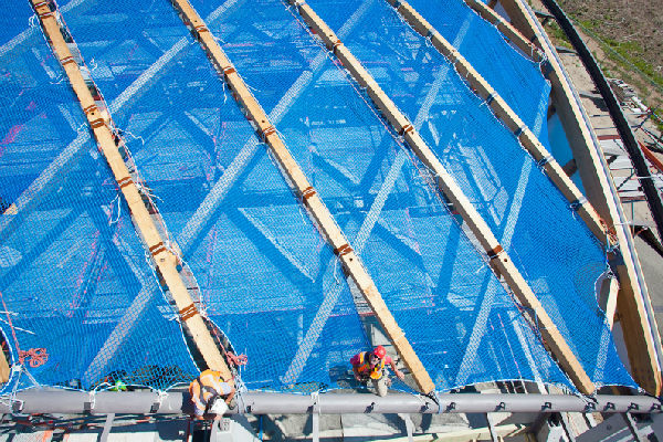 Net work: Coastlands Aquatic Centre roof workers supported by a swathe of blue safety net at the site last week.
