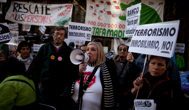 POVERTY PROTEST: Mortgage Victim Platform member Marta Uriarte, who has stopped the auction of her home three times, speaks outside Caja Madrid Bank main office in Madrid.