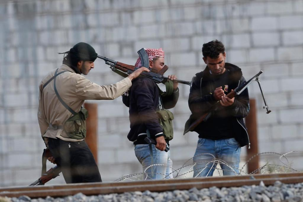 Free Syrian Army fighters check their machine guns in the Syrian town of Ras al-Ain, as seen from the Turkish border town of Ceylanpinar.